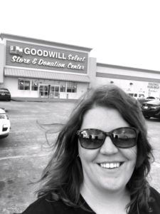 Black and white photo of author outside entrance of thrift store.