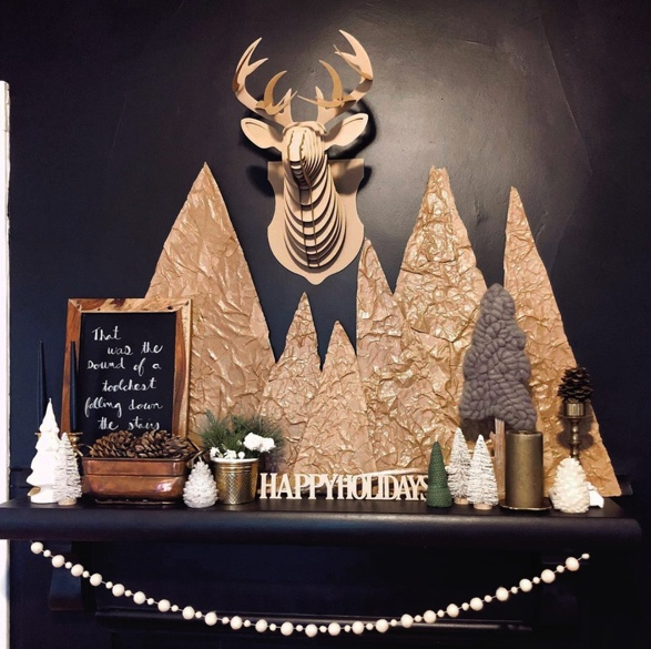 Holiday fireplace mantle featuring a cardboard faux deer bust